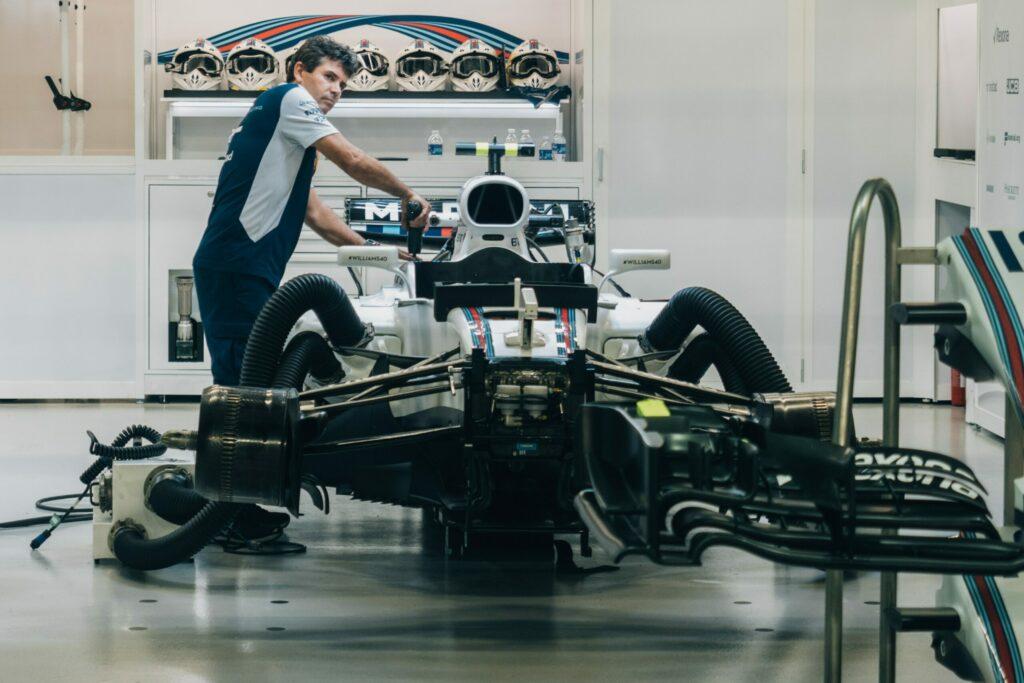 man standing beside formula car